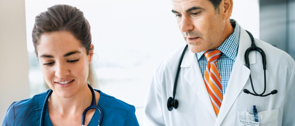 Physician with iPad in hand talking with Nurse